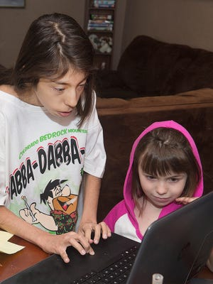 In this Feb. 1, 2018, photo, Sally Padilla, left, works on her laptop at home while Isabella, 6, one of the younger members of the Padilla household watches in Pueblo, Colo. Sally, 16, is a student of Pikes Peak Online School, a virtual institution that provides individualized online education to young Coloradoans for whom a traditional public classroom isn't a good fit. (Chris McLean/The Pueblo Chieftain via AP)