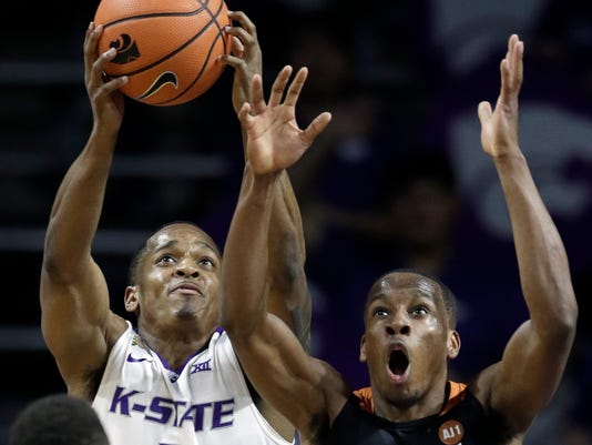 Kansas State guard Barry Brown (5) rebounds against Texas guard Matt Coleman, right, during the first half of an NCAA college basketball game in Manhattan, Kan., Wednesday, Feb. 21, 2018. (AP Photo/Orlin Wagner)