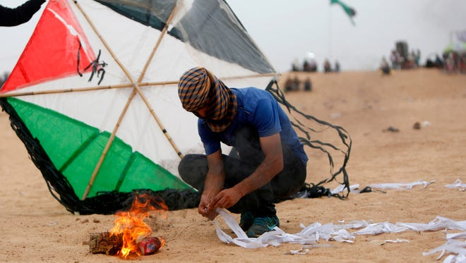 Palestinians prepare an incendiary device attached to a kite before trying to fly it over the border fence with Israel, on the eastern outskirts of Jabalia, on May 4, 2018.