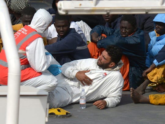 Rescued migrants talk to a member of the Malta Order after a fishing boat carrying migrants capsized off the Libyan coast, is brought ashore along with 23 others retrieved by the Italian Coast Guard vessel Bruno Gregoretti at Boiler Wharf, Senglea in Malta on April 20, 2015. More than 700 people are feared dead following the capsize off Libya of a fishing boat that had been crammed with migrants trying to reach Europe.