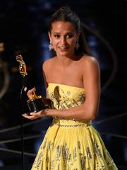 Alicia Vikander accepts the Oscar for best supporting actress at the Oscars.