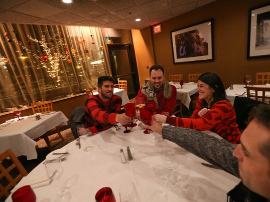 Writer Adena Miller, second from right, and friends Andy Villa, right, Jake Purcell, second from left, and Guido Cristofori, share a toast at their final stop of the night, Max of Eastman Place during their December food crawl around the East End in downtown Rochester Monday, Dec. 12, 2017.