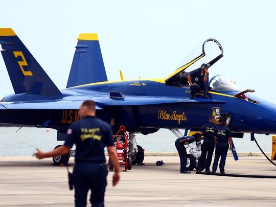 Blue Angel crew members inspect a F/A-18 Hornet before