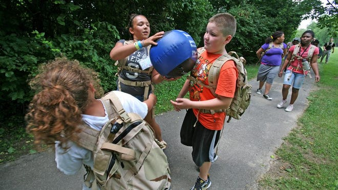 Rileigh May, 11, passes a medicine ball to Sam Ryan, 10, on a hike at the Forever-Fit Summer Camp in 2011. The Children's Better Health Institute runs the six-week camp which exposes kids ages 8 to 12 to a variety of physical activities, and teaches them about good nutrition and eating. The camp is designed for kids dealing with being overweight or obese.