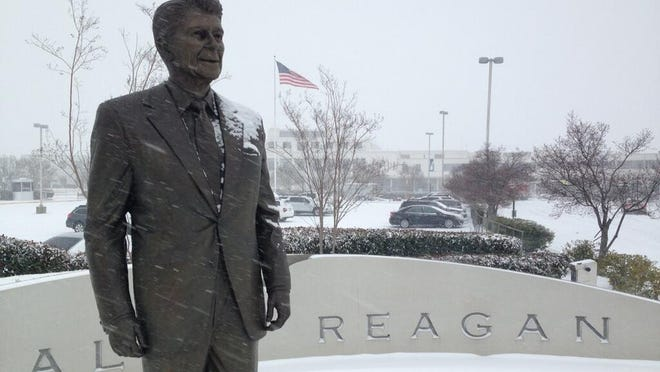 A statue of President Ronald Reagan on the grounds of the D.C. airport the bears his name receives a fresh coat of snow on Monday, March 3, 2014.