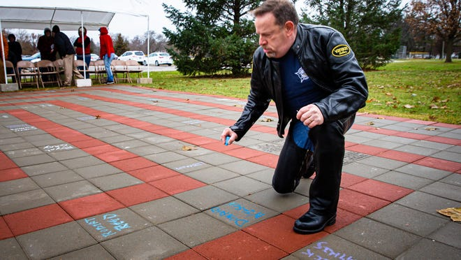Brad Green, who has been living with HIV since 1988, writes down the names of friends who have lost their lives to HIV/AIDS among the bricks of the AIDS Memorial Labyrinth during a Service of Remembrance held to coincide with World AIDS Day in Lincoln Park, Sunday, Dec. 1, 2019, in Springfield, Ill.