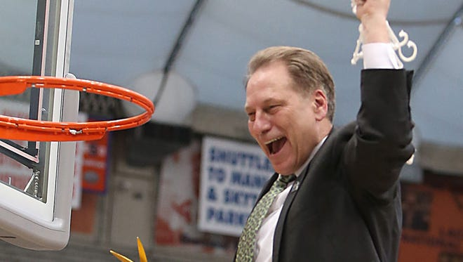 Michigan State head coach Tom Izzo celebrates with his team after the 76-70 overtime win against the Louisville Cardinals.