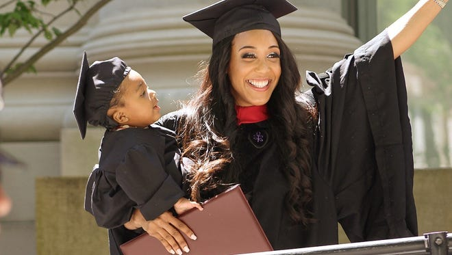 Briana Williams walks across the stage at Harvard Law School graduation with her daughter Evelyn.