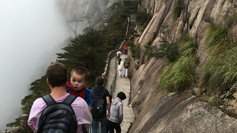 Dean Overlin carrying his son, Jaylen, on the Yellow Mountain trail in China.