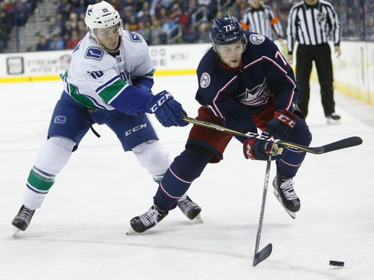 Vancouver Canucks' Jake Virtanen, left, slashes Columbus Blue Jackets' Josh Anderson during the second period of an NHL hockey game Friday, Jan. 12, 2018, in Columbus, Ohio. Virtanen was penalized on the play. (AP Photo/Jay LaPrete)