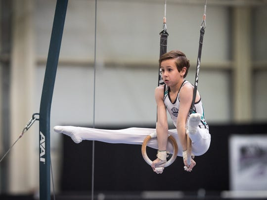 Granville Middle School seventh grader Aiden Bennett competes on the rings during a recent meet.