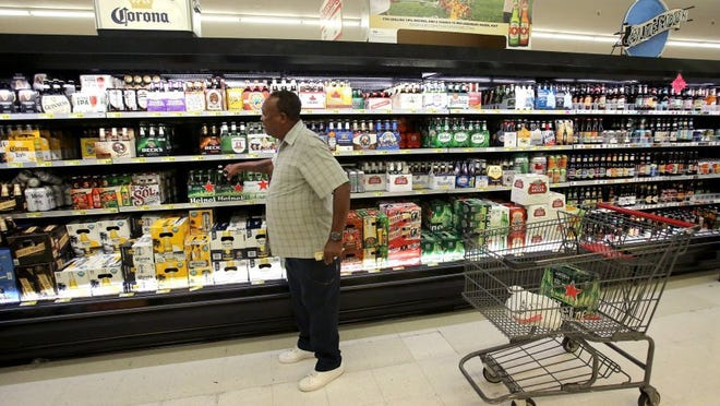 June 30, 2016 — Larry Jackson makes a selection from over 300 beers at the Cash Saver in Midtown. Grocery stores across Tennessee can sell wine starting Friday, July 1. Beer sells will continue with a 'by volume' cap of 6.2; beginning next year the cap will be 10.2. (Stan Carroll/The Commercial Appeal)