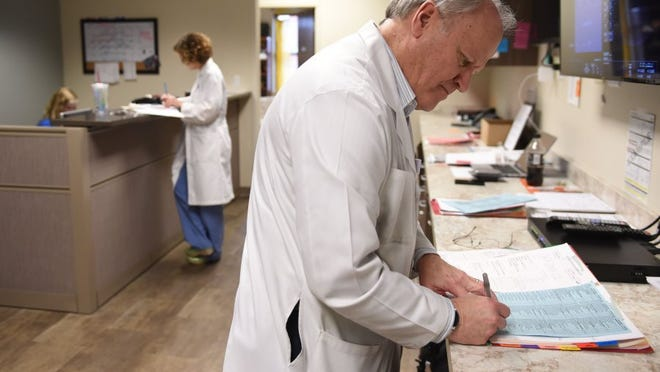 Dr. Craig Towers makes notes between seeing patients from his practice at High Risk Obstetrical Consultants Feb. 23, 2016.