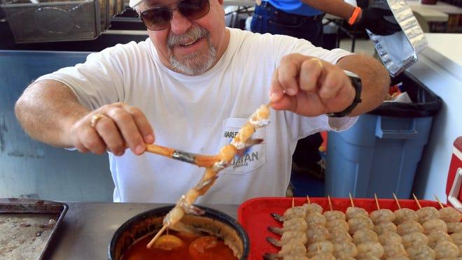GABE HERNANDEZ/CALLER-TIMES Peter Grish prepares shrimp skewers for customers during Shrimporee on Saturday, June 11, 2016, in Aransas Pass.
