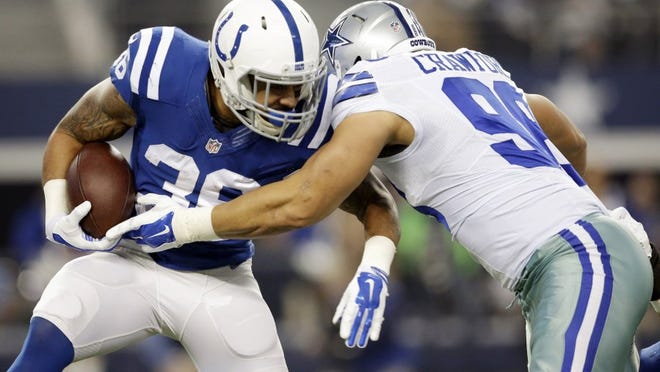 Indianapolis Colts running back Dan Herron (36) is tackled by Dallas Cowboys defensive tackle Tyrone Crawford (98) after a short run during the first half of an NFL football game, Sunday, Dec. 21, 2014, in Arlington, Texas. (AP Photo/Tim Sharp)