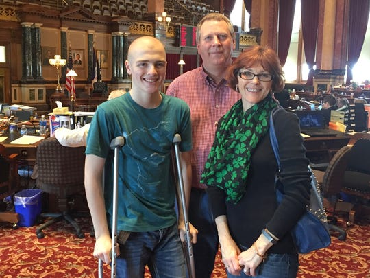 Jacy McAlexander, 15, with his mother and father, Earl and Kerri, during a visit to the Iowa Senate chamber Wednesday afternoon. The youth climbed to the top of the Iowa Capitol dome Wednesday despite having a fractured leg and recently being diagnosed witih bone cancer.