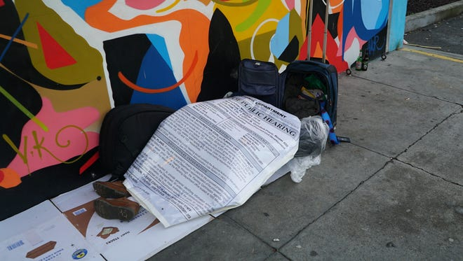 """A homeless man sleeps on the street, covered by a large sign advertising a new development proposed for the site of the former Flax Art & Design store. The nine-story building in the Market and Octavia area of central San Francisco will contain about 160 apartments, with 19 of those designated as """"affordable."""""""