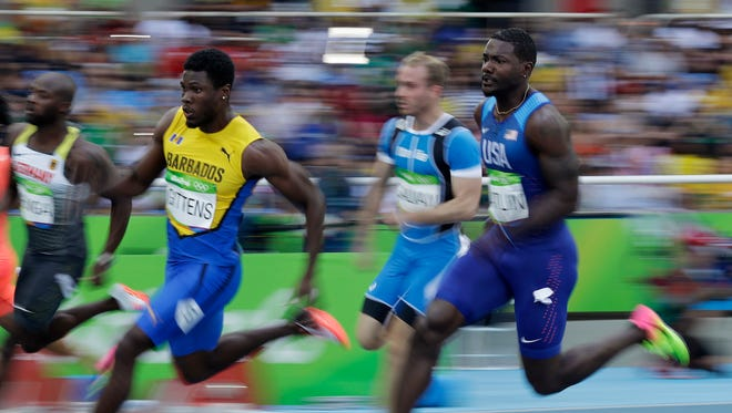 United States' Justin Gatlin, right, and Barbados' Ramon Gittens, left, compete in a men's 200-meter heat during the athletics competitions of the 2016 Summer Olympics at the Olympic stadium in Rio de Janeiro, Brazil, Tuesday, Aug. 16, 2016. (AP Photo/Matt Dunham)