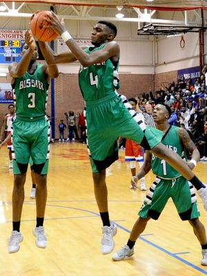 Bossier's Kalaas Roots (4) grabs a rebound as Dante Bell (3) and Jacoby Decker (1) look on during their game at Woodlawn Tuesday evening.