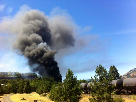 A train towing cars full of oil sends up a plume of smoke after derailing Friday, June 3, 2016, near Mosier, Ore., by the scenic Columbia River Gorge. The accident happened just after noon about 70 miles east of Portland. It involved multiple cars filled with oil, and one was burning. Highway 84 was closed for a quarter-mile near the site, and the radius for evacuations was a half-mile. (Mark B. Gibson/The Dalles Chronicle via AP) MANDATORY CREDIT