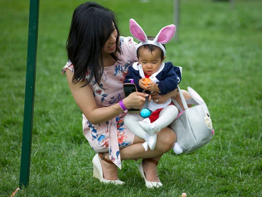 Eleven-month-old Victoria Cheng and her mother Guliana Cheng, both from San Francisco, prepare to participate in the White House Easter Egg Roll on the South Lawn of the White House in Washington, Monday, April,17, 2017. President Donald Trump and first lady Melania Trump are set to host the official annual Easter egg roll at the White House.