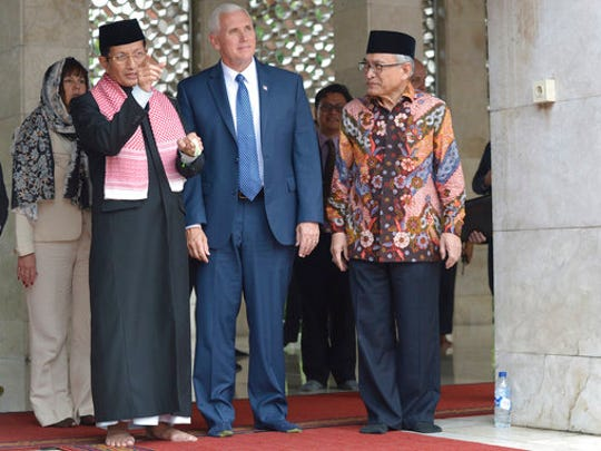 U.S. Vice President Mike Pence, center, is given a tour by the Grand Imam of Istiqlal Mosque Nasaruddin Umar, left, and the Chairman of the mosque Muhammad Muzammil Basyuni, right, during his visit to the largest mosque in Southeast Asia, in Jakarta, Indonesia, Thursday, April 20, 2017. Pence praised Indonesia's democracy and moderate form of Islam after meeting Thursday with the president of the world's most populous Muslim nation.