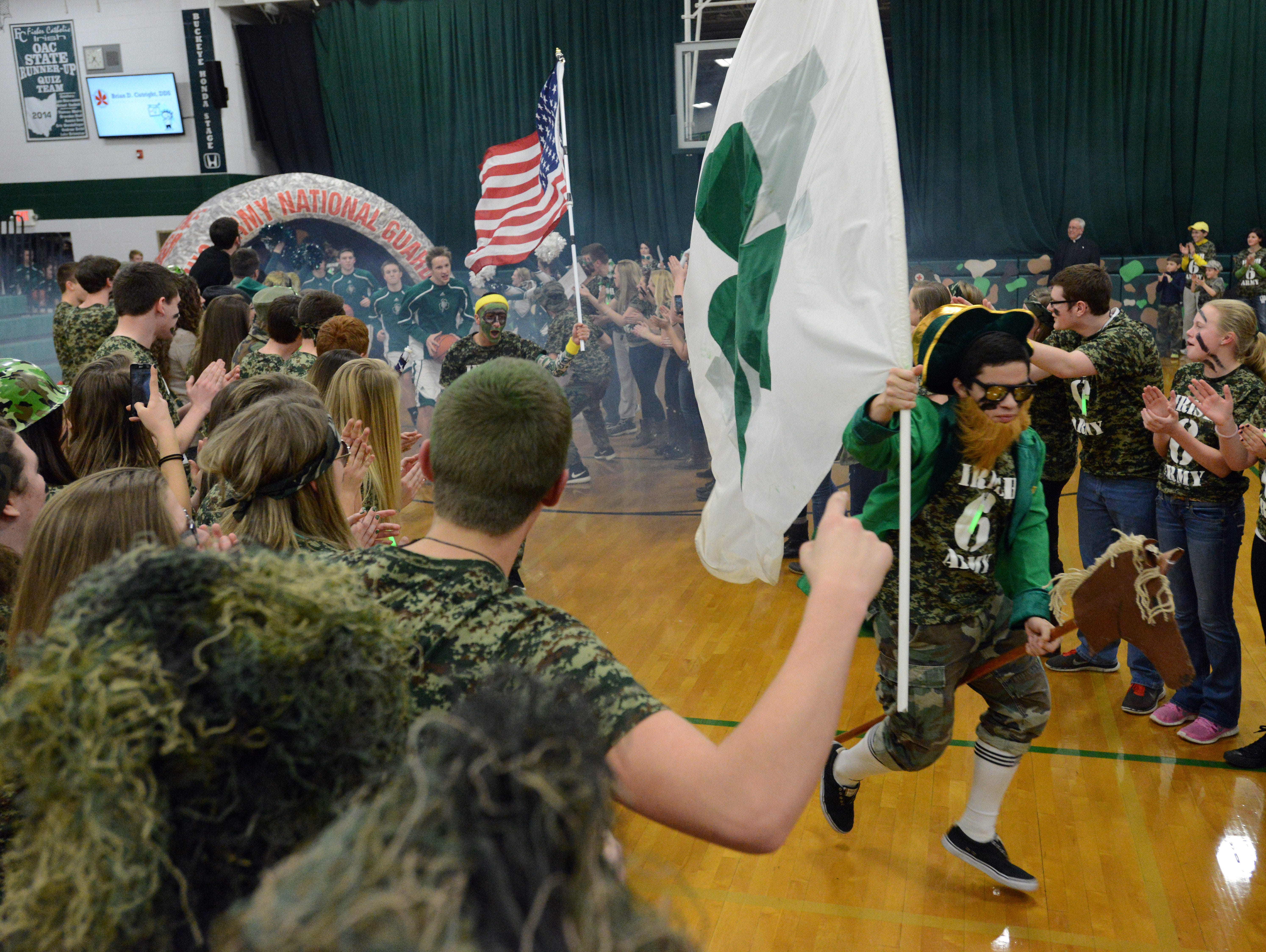 The Fisher Catholic student section form a tunnel for the boys varsity basketball team to take the court Feb. 6 in Lancaster.