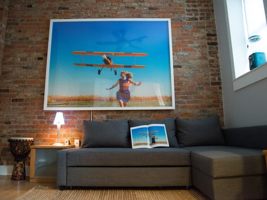 "A mock Time magazine signed by artist Tyler Shields sits under the blown-up print of his ""Girl Running from Plane"" in a small sitting space to the side of the entrance. Exposed brick is original to the building."