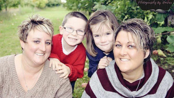 Heather McBride, left, and Crystal Miller with their children Caiden, 7, and Riley, 8. Only Crystal Miller is the legal parent of the two adopted children.