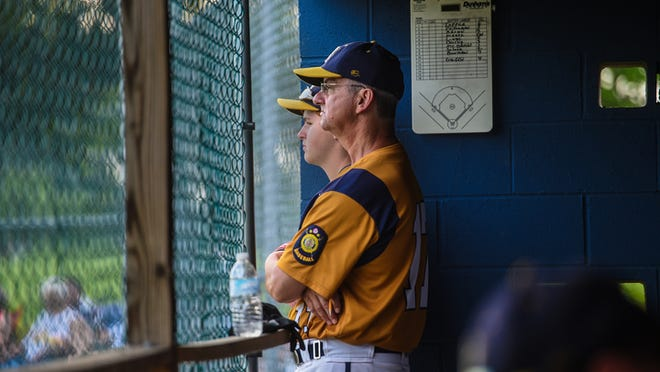 Hanover American Legion coach and statistician Jeff Miller stands in the dugout with player Nevada Day during Thursday's game against Dallastown. Miller has been an assistant for 33 years, and Thursday was his 700th consecutive game.