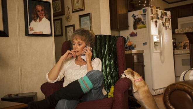 Lea Anne Shellberg talks on the phone in her home in Fort Collins. A single mother who is disabled because of a work injury, Shellberg often struggles to pay her utilities on her fixed income. On this day, her mother, whom Shellberg cared for at home for many years before moving into a nursing home, was ill, and Shellberg made several calls to the nursing home and other family members, trying to find out what was wrong.