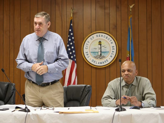 H. Jeff Sturdevant (standing), principal manager of GHD, the company overseeing the Rehoboth Beach ocean outfall project, prepares to open the three bids submitted by companies for the main construction of the project.