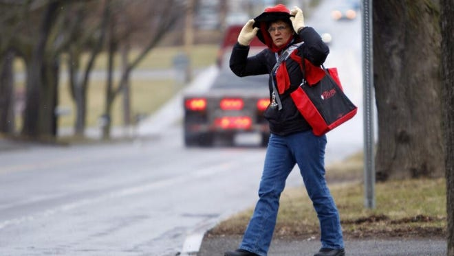 In this file photo, Carol Spath of Hilton bundles up to brave cold, windy weather.