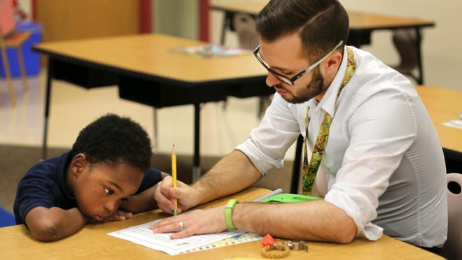 Kindergartner Montayo Turner-Ford works on his letters with teacher Brandon Fremming at Ethel M. Taylor Academy, a CPS school in Millvale. On June 24, 2019, the school board approved a $657-million budget, increasing funding to serve more students by hiring more teachers, adding more classrooms, and creating more individualized educational options.