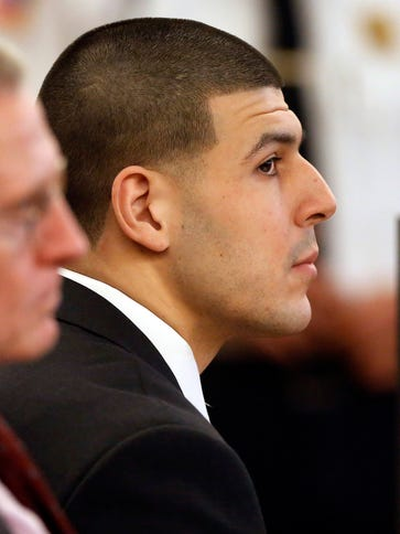 Aaron Hernandez, right, listens during his murder trial
