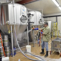 Beaver Island Brewing brewmaster Chris Laumb washes down the exterior of a fermenter. The brewery is releasing a new beer Wednesday.