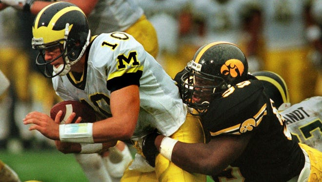 Former Iowa player Anthony Herron, seen here sacking Tom Brady in a 1998 game, works for the Pac-12 Network.