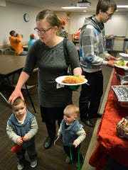 As the Berryhills spend Christmas Day at the Neonatal Intensive Care Unit on Friday, Dec. 25, Denise Berryhill ferries her two older boys, Joel, 2, and Marcus, 1, back to a table as dad, Dan, loads up a few more plates of food. Just North of Memphis BBQ & Catering of Clearwater donated and catered a meal in for the families at the NICU. The Berryhills' youngest child, Seth, has spent 60 days in the NICU.