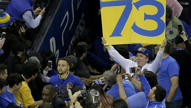 A Golden State Warriors fan holds up a 73 sign as Golden State guard Stephen Curry (bottom left) runs out of the tunnel before the Grizzlies' game against the Warriors on Wednesday, April 13, 2016. The Warriors had 72 wins heading into their final regular-season game, the same number of wins as the 1995-1996 Chicago Bulls. (AP Photo/Jeff Chiu)