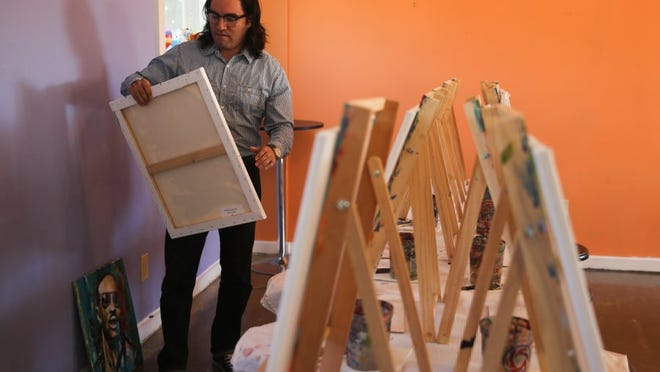 Alejandro Castanon removes a painting Wednesday in preparation of the upcoming Nude Art Show at Vino Dipinte Art Gallery, 602 Orient St. The opening reception is 6-10 p.m. Saturday. Yfat Yossifor/Standard-Times