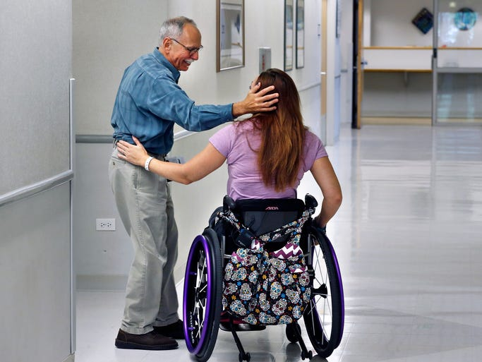 Olympic swimmer Amy Van Dyken-Rouen talks with Craig Hospital Director of Phychology Dr. Lester Butt before leaving the hospital in Englewood, Colo., Thursday, Aug. 14, 2014. Van Dyken-Rouen was left paralyzed just below the waist in an all-terrain vehicle crash on June 6 in Arizona. (AP Photo/Brennan Linsley)