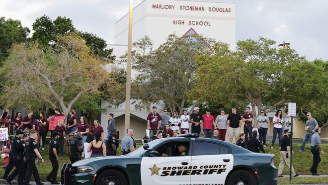 In this Feb. 28, 2018 file photo, a police car drives near Marjory Stoneman Douglas High School in Parkland, Fla., as students return to class for the first time since a former student opened fire there with an assault weapon.