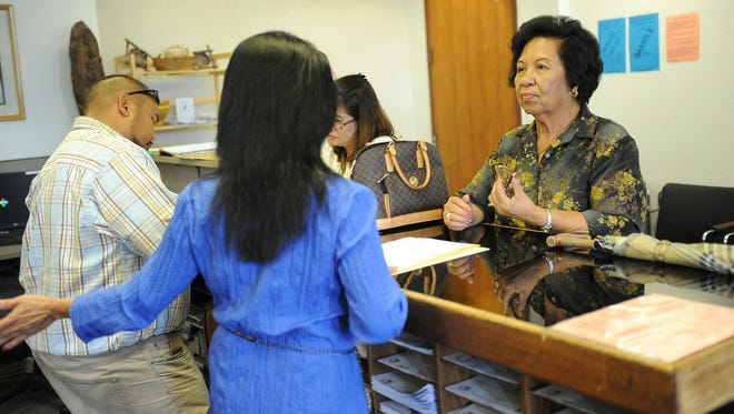 Agana Heights resident Glorina Perez, right, and Dededo resident Concepcion Villena, background, receive instructions as they receive ballots  at the Guam Election Commission in 2012. The residents were voting early at the GEC office for the primary election.