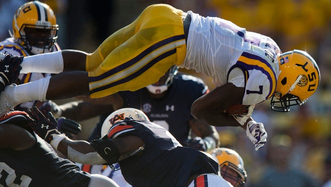 Louisiana State running back Leonard Fournette  leaps over Auburn Tigers defenders to score a touchdown during the NCAA football game between LSU Tigers and Auburn on Saturday, Sept. 19, 2015, at Tiger Stadium in Baton Rouge, La. LSU Tigers defeated Auburn Tigers 45-21.