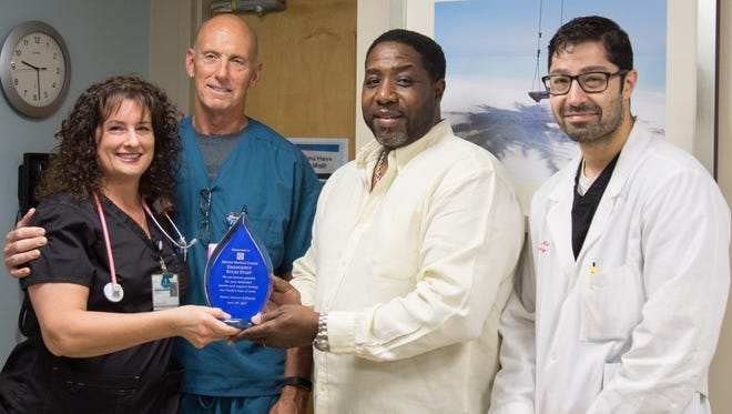 Robert Stewart reunites with three of the emergency department clinicians who cared for him at Martin Medical Center (from left) Nurse Vicki Lingner; Nurse Robert Baker; and Dr. Nathaniel Moseni.