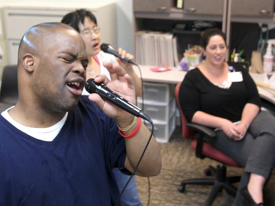 "Dion Wiggins, front, sings a karaoke duet to Mariah Carey's ""One Sweet Day"" with Kimber Louderhose while Program Manager Megan Feeney listens in Monday, May 2 in Fort Myers."