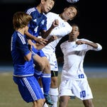Lakeland's Cody Tiedeman (center, white jersey) goes head-to-head with Walled Lake Western's Allen Zhao (4) for a head-ball during Tuesday's division clinching win. Lakeland's Tyler Green is at lower right.
