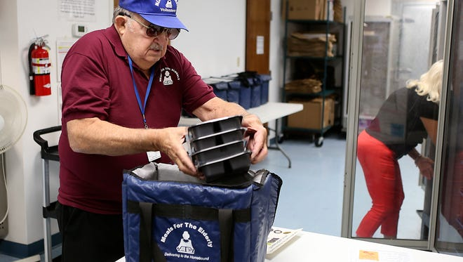 Volunteer Ray Favre packs prepared meals for his morning route with Meals for the Elderly, Friday, Oct. 6, 2017.