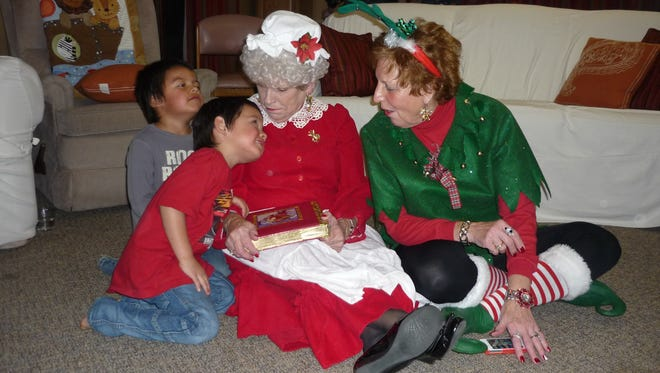 Two children tell Mrs. Claus, a House of Hope volunteer, and her elf what they would like for Christmas.