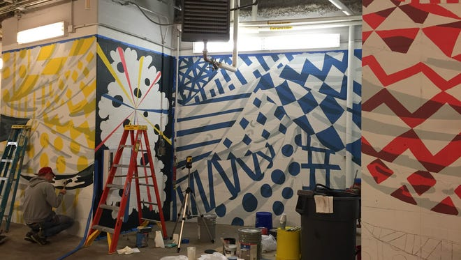 Artist Michael Stillion, lower left, works on a mural for the temporary entrance at the Contemporary Arts Center.